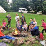 Students toasting marshmallows at a campfire