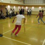 Students playing cricket in the sports hall