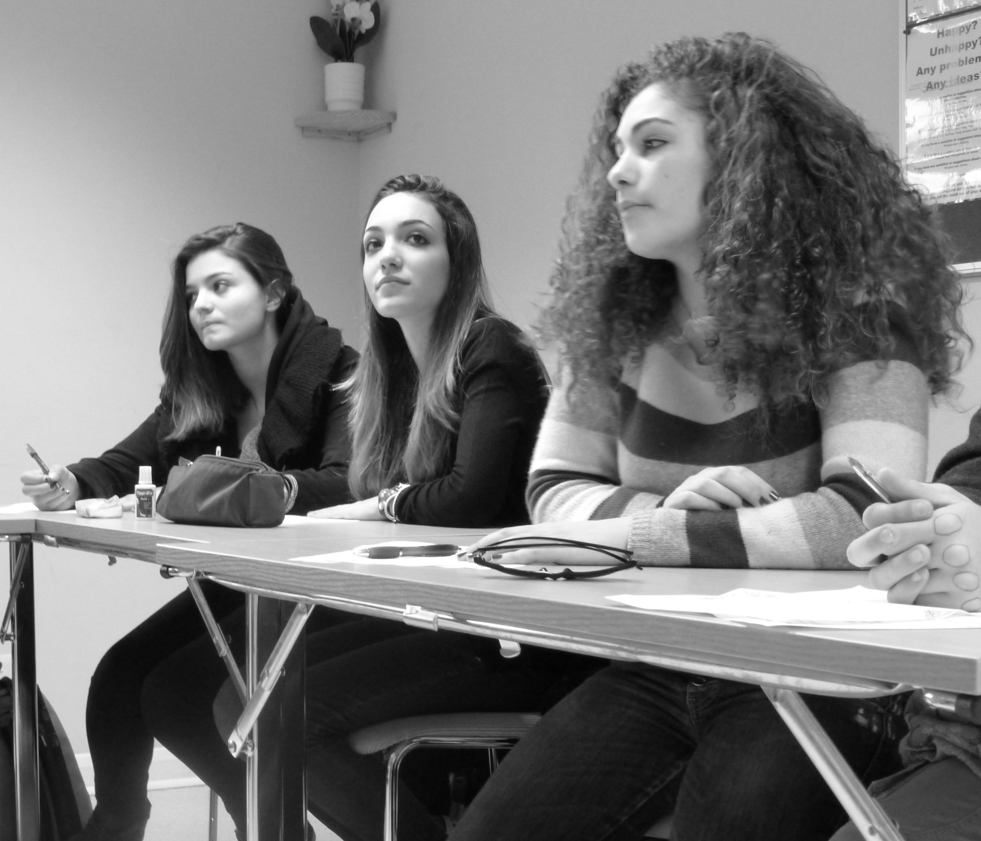 Black and white photo of 3 female students in class