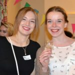 2 female students drinking wine at a party