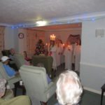 School choir singing Christmas songs in an old peoples home