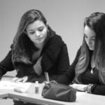 Black and white photo of 2 female students doing class work