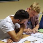 2 male students helping each other with work