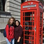 Students in London standing next to the iconic red pillar telephone box