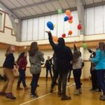 Students in the gym at loxdale throwing baloons