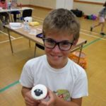 pre-teen boy young learner posing with a cupcake he has made